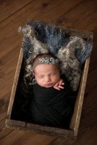 Newborn baby in a beautiful wooden box