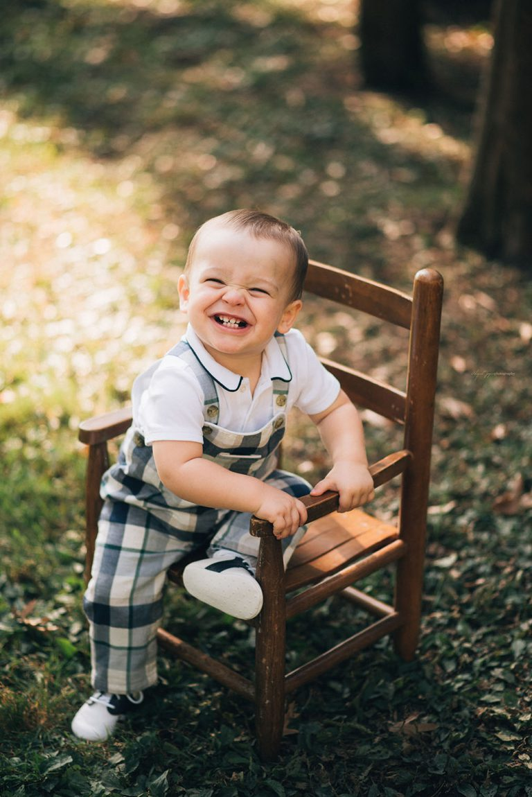 baby with big smile while sitting on rocking chair