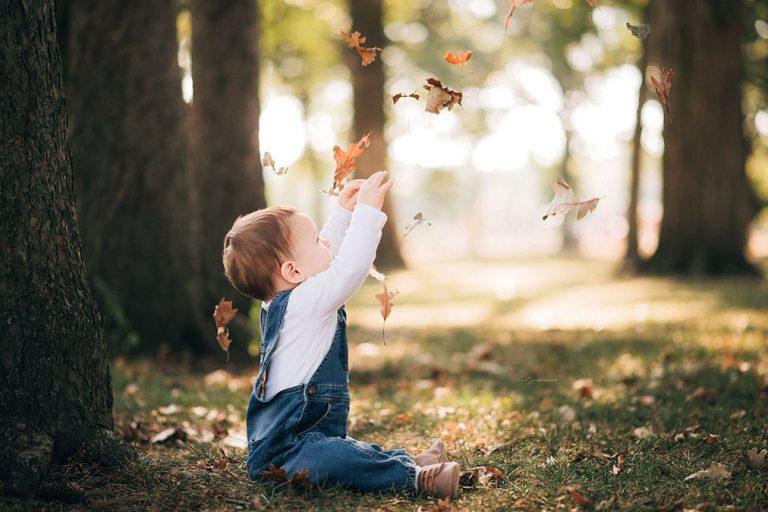 Baby grabbing at fall leaves