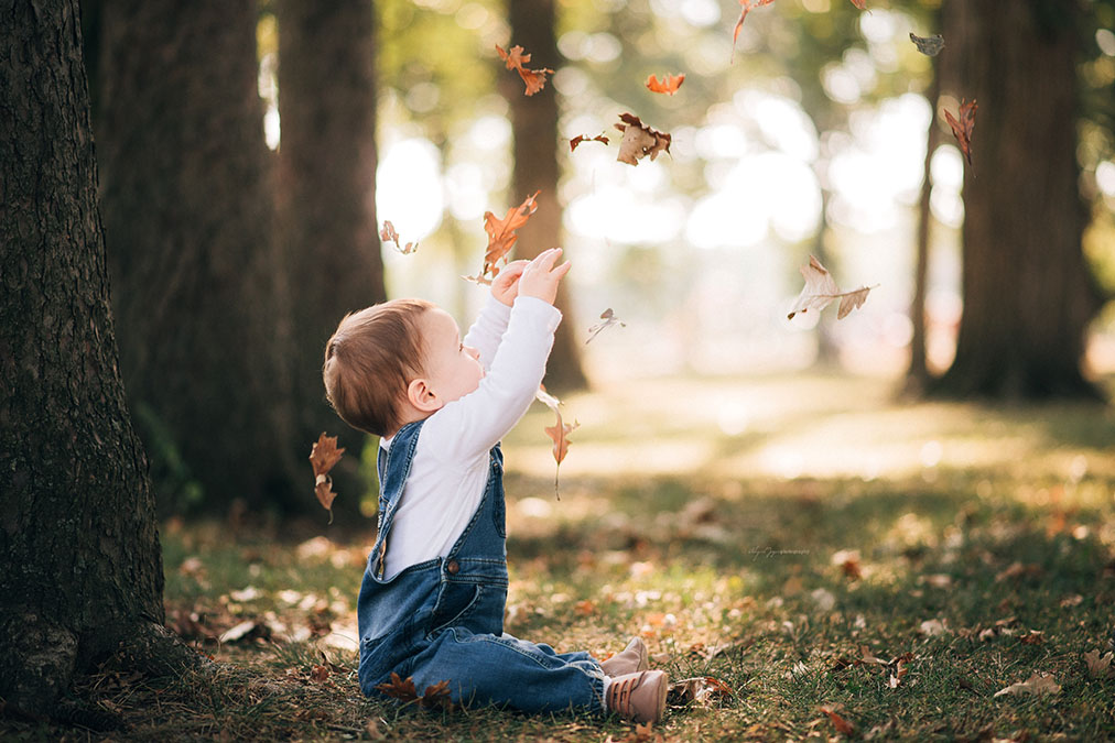 A baby boy throws leaves into the air during a portrait session