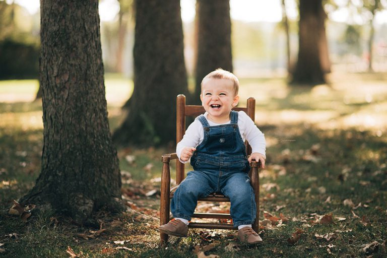 little baby smiling while sitting on chair