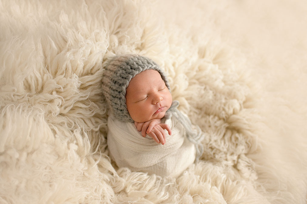 newborn baby swaddled and laying against a Flokati rug