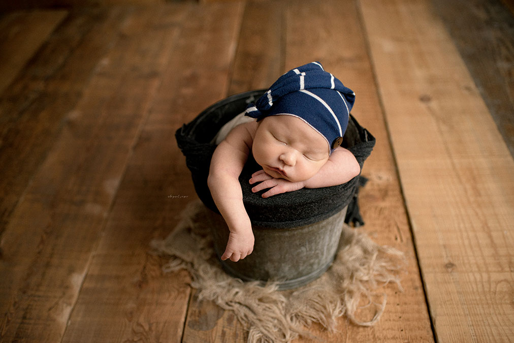 Newborn in bucket against hardwood floor