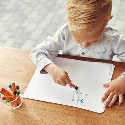Little boy writes on paper with a crayon