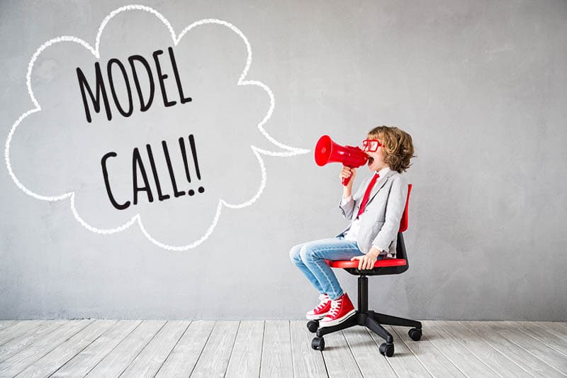 """Little boy on rolling chair with megaphone and words saying """"Model call"""" against grey background."""
