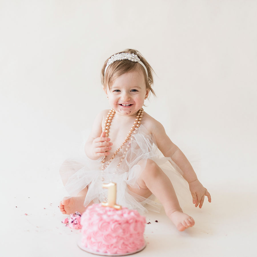 a 1 year old girl smiling during her cake smash children's photography session