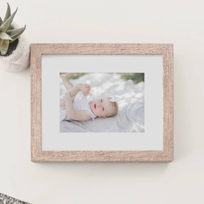 A baby photograph in a wood frame sitting on a table.