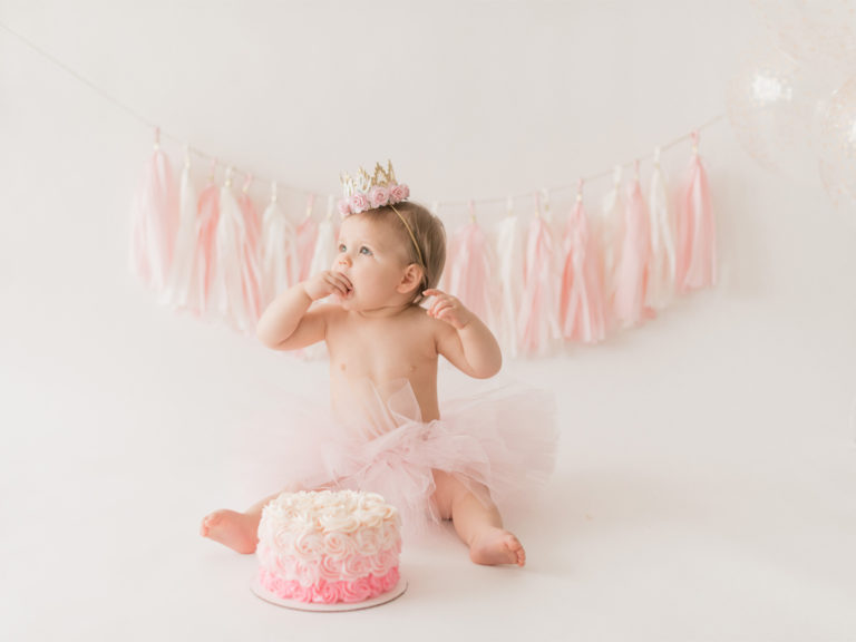 Child girl cake smash in tutu and crown with props