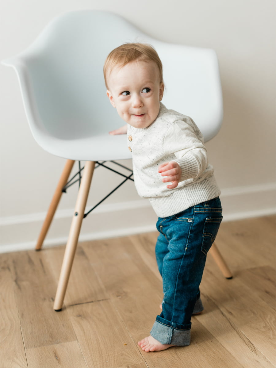 Child by chair during studio photo session