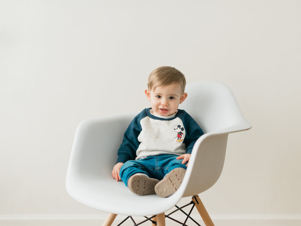 Child sitting in a white chair photo session