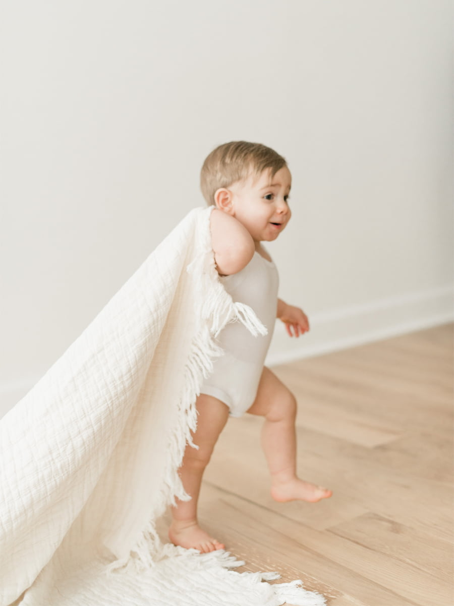 Boy pulling blanket in studio photo session