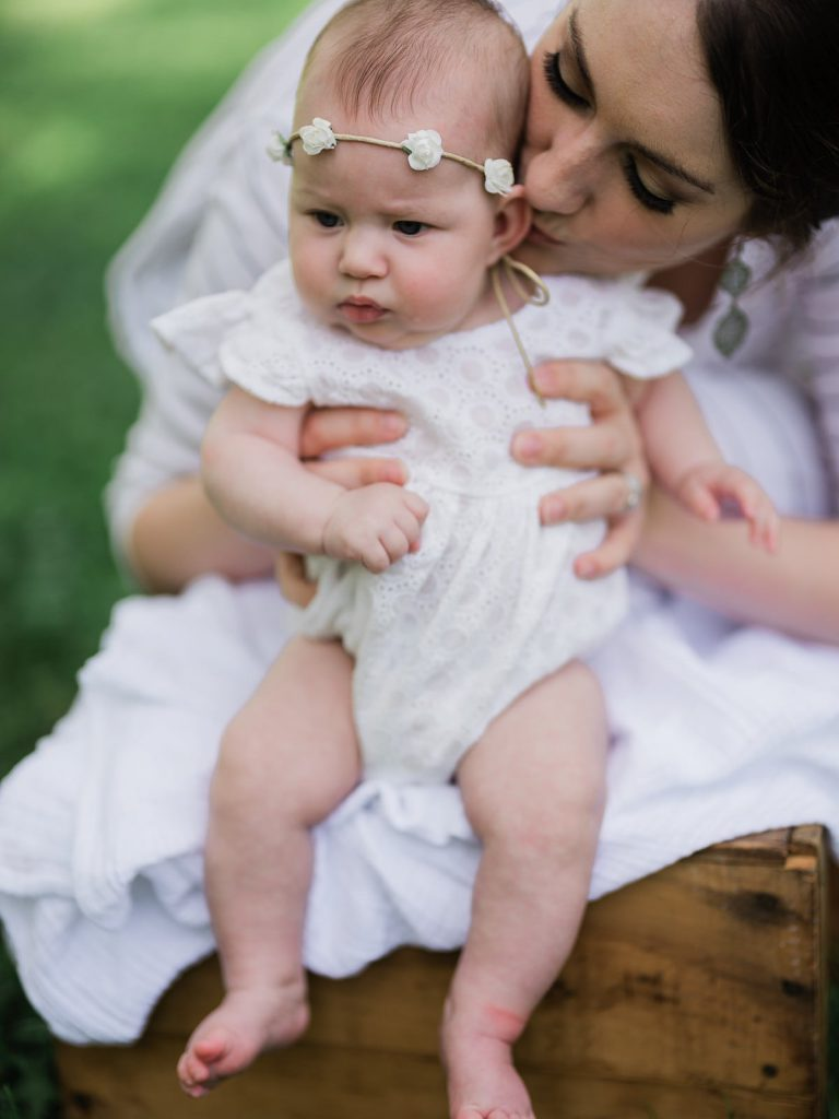 A young baby girl in a white onesie is being held by her mother who kisses her ear