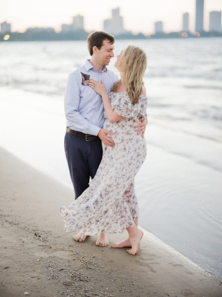 an expecting mother and father stand in the sand against the chicago skyline as they pose for their maternity portraits